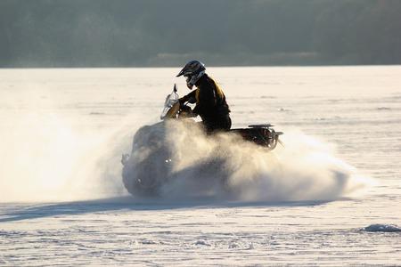 Quad bikes driver rides over frozen lake.