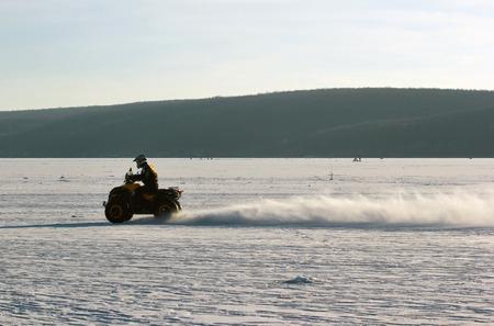quad: Quad bikes driver rides over frozen lake.