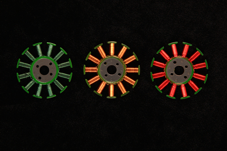 windings: Red yellow and green windings on coil assemblies of brushless motors against the black background