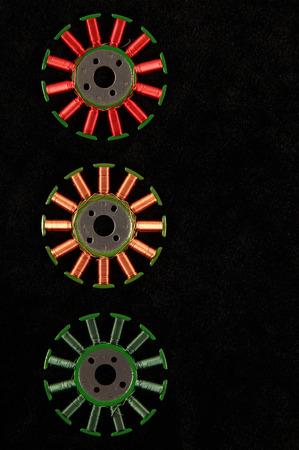 windings: Copper windings of old motor stators against the black background