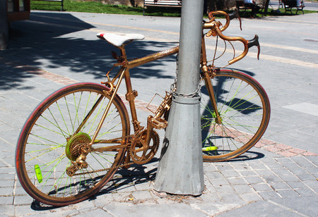 chained: Golden painted bicycle chained to a street lamppost Stock Photo