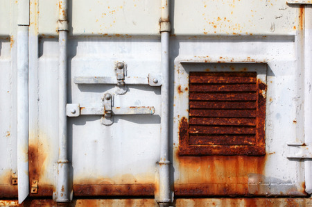 grille': Fragment of a door of old sea shipping container. Rusty ventilation grille and flaking white paint.