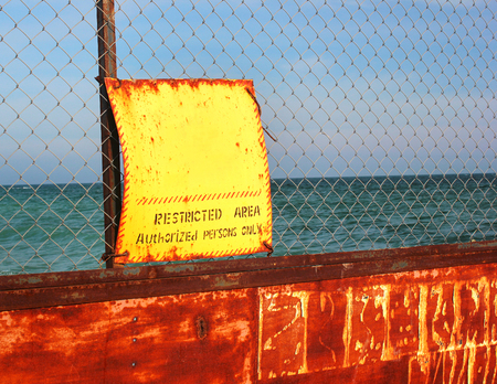 prosecute: Old rusty wire fence with yellow warning sign against sea background indicating restricted area of the beach Stock Photo