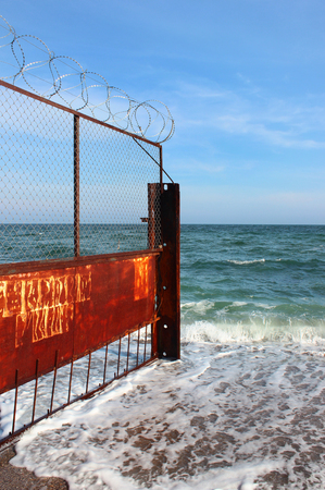 prosecute: Old rusty wire fence on a seashore. Restricted area on a beach