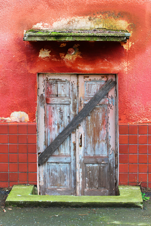 tatty: Weathered wooden doors in red wall, closed and boarded up