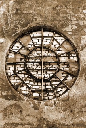 gentrification: Bricked up round window in old grungy wall Stock Photo