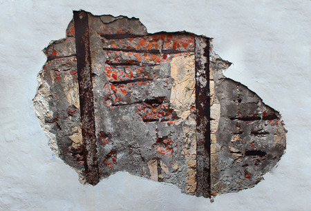 armature: Grunge red brick wall background texture with weathered damaged pitted concrete rusty armature and peeling plaster and flaking paint Stock Photo
