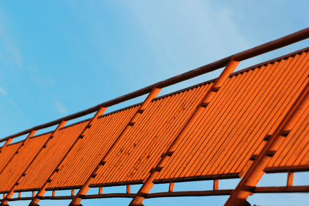 hand rail: Orange painted metal fence against blue sky background, perspective view. Focus is in the middle Stock Photo