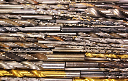 driller: Many old dirty used metal drill bits as background