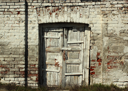 tatty: Old weathered wooden door in brick wall Stock Photo