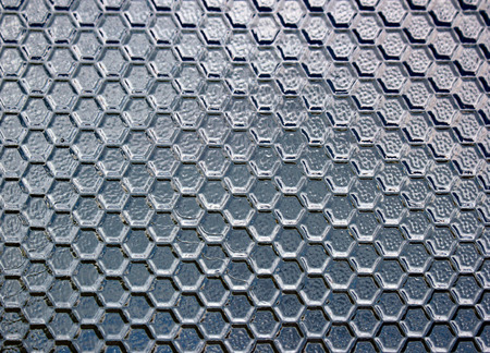 semitransparent: Stained textured semitransparent glass background. Bright reflections and deep shadows on honeycomb pattern Stock Photo