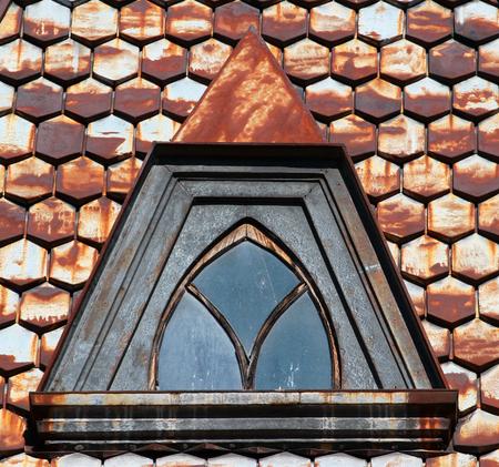 attic window: Rusty metal shingle roofing with attic window closeup Stock Photo
