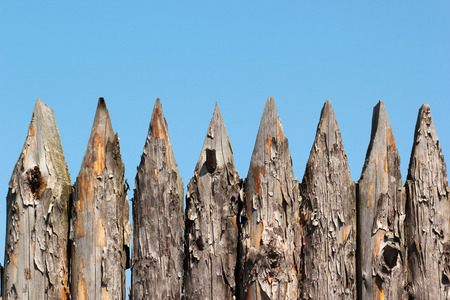trespass: Stockade wooden fence on blue sky background Stock Photo