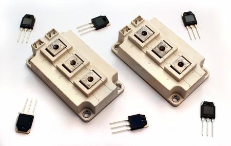Potentes módulos IGBT de transistores y transistores pequeños en el fondo blanco