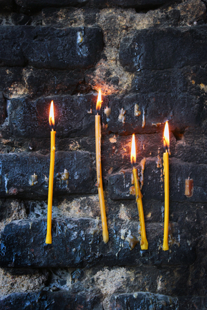 sooty: Four burning candles on old sooty blackened stone wall