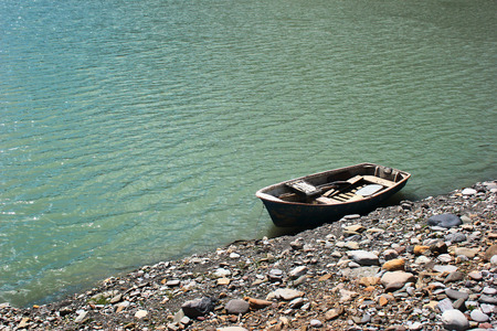 punt: Lone punt boat on rocky lake shore