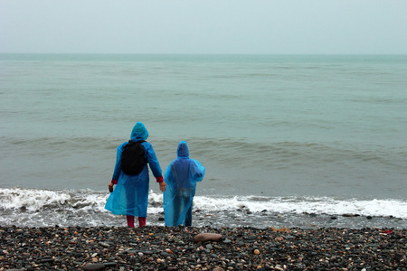 Woman and girl in raincoats looking at the cold sea. Rainy day, inclement weather on a beach Stock Photo