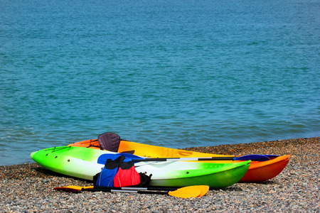 paddles: Two colorful sea kayaks with paddles and life jackets on stony beach