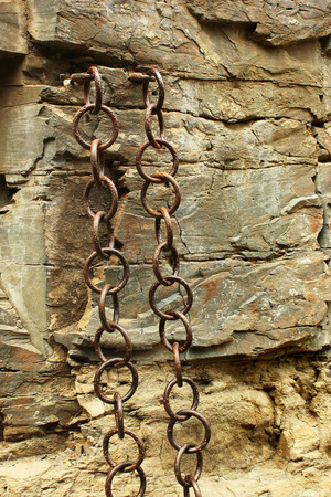 enchain: Old metal chains in the rough stone wall Stock Photo
