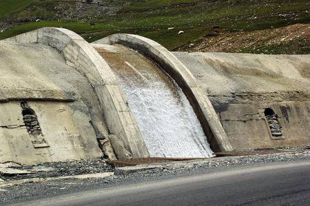 runoff: Concrete weir on Tergi river in mountainous area near Georgian Military Road, Caucasus mountains, Georgia Stock Photo
