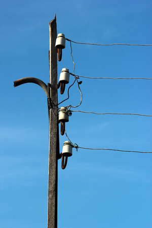 Wires and power line insulators disks on electrical pole Stock Photo