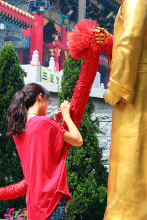matchmaker: HONG KONG, MARCH 22, 2012: Young woman ties red string to Statue of Yue Lao, or old man under the moon, chinese god of marriage at Sik Sik Yuen Wong Tai Sin Taoist Temple in Kowloon, Hong Kong.