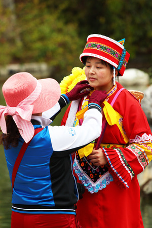 SHILIN, CHINA - MARCH 7, 2012: Chinese tourists visiting the Stone Forest dress in traditional costumes of the Sani ethnic minority group, Shilin, Yunnan, China.