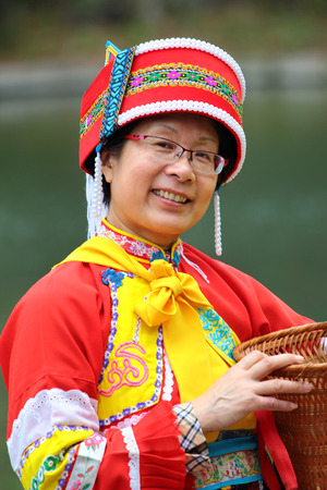 SHILIN, YUNNAN, CHINA - MARCH 7, 2012: Beautiful woman of Sani people in colorful traditional costume. The Sani is a small ethnic group from Yi minority of Southern China. Editorial