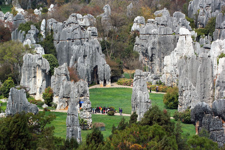 Tourists in Shilin stone forest, world-famous natural area of limestone formations and UNESCO World Heritage Site, Yunnan, China.