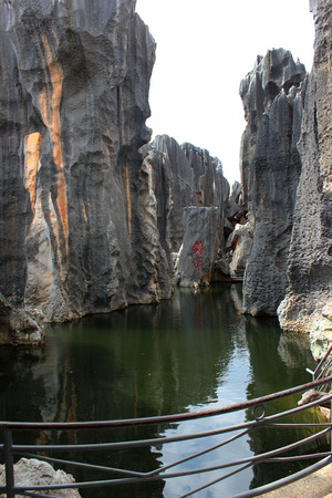 Pond in Shilin stone forest, world-famous natural area of limestone formations and UNESCO World Heritage Site, Yunnan, China. Sword Peak is written in Chinese. Stock Photo