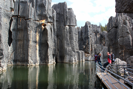 SHILIN, CHINA, MARCH 7, 2012: Tourists on Sword Peak Pond in Shilin stone forest in Yunnan province, world-famous natural area of limestone formations