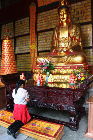 GUANGZHOU, CHINA, MARCH 5, 2012: Young woman prays in Big Buddha Temple (Da Fo Si), one of five renowned Buddhist temples in Guangzhou. The three bronze Buddha statues represent the past, present and future.