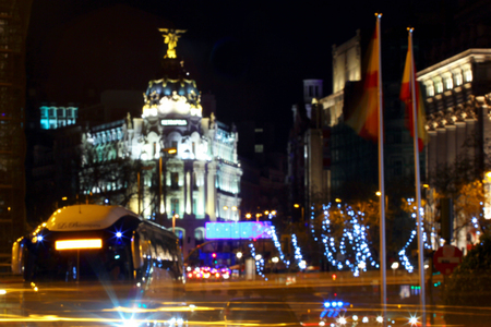 Blurred rays of traffic lights on Gran via street, main shopping street in Madrid at night. Spain, Europe.