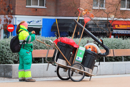 MADRID, SPAIN - DECEMBER 15, 2016: Street and park cleaner woman with her equipment in Madrid Rio park. Madrid has the most green areas in Europe.