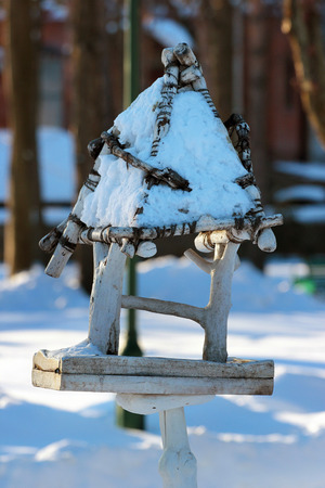 Empty wooden bird feeder in a park at wintertime