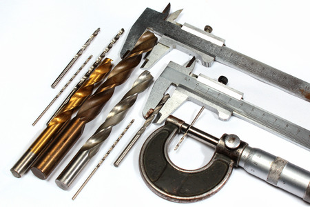 Drill bits and micrometer screw caliper on white background Stock Photo