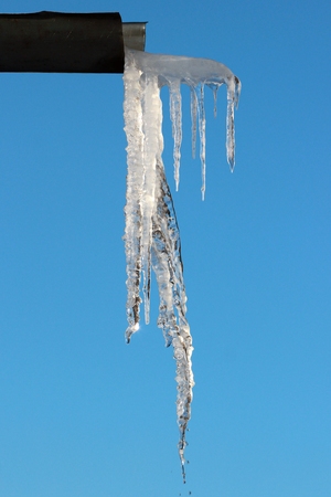 Melting icicle on a gutter Stock Photo