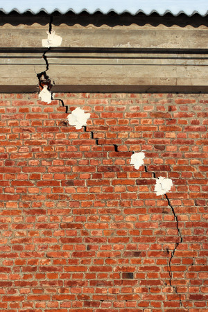 Crack in a brick wall. Alebaster markers are applied to check if crack gets wider as time goes on.  Stock Photo