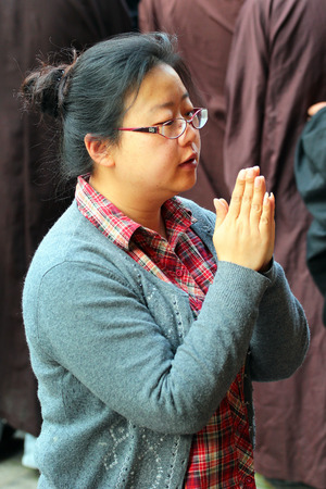 KUNMING, CHINA - MARCH 14, 2012: Young woman holds her hands in anjali mudra, praying at Yuantong monastery, oldest and most famous temple in Kunming, Yunnan.