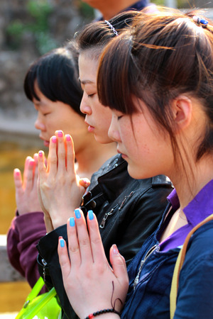 KUNMING, CHINA - MARCH 14, 2012: Young women hold hands in anjali mudra, praying at Yuantong monastery, oldest and most famous temple in Kunming, Yunnan.