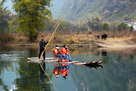 YANGSHUO, CHINA - MARCH 16, 2012: Girls going down the Yulong river on bamboo raft near Yangshuo town. Rafting is very popular attraction among tourists. Editorial