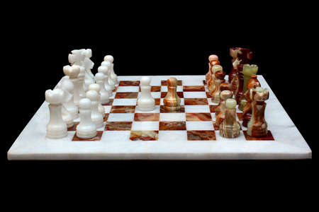White marble and onyx stone chessboard with pieces, isolated on black background