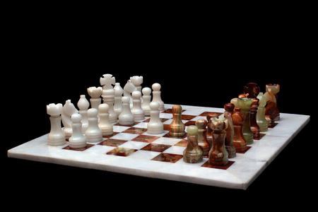 domination: White marble and onyx stone chessboard with pieces, isolated on black background