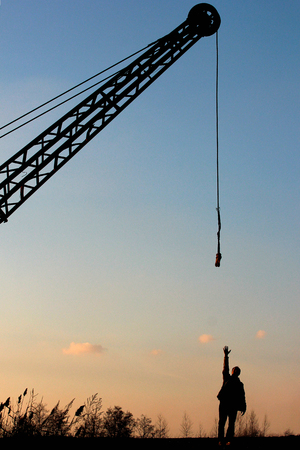 Man stretches his hand trying to reach hanging crane rope