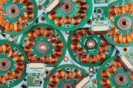 windings: Many printed circuit boards from old floppy drives with windings and coils of brushless motors. Abstract electronics background.