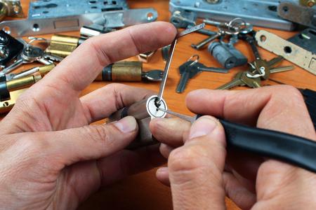 Cerrajero recoge una cerradura de cilindro con cerradura y llave de tensión Foto de archivo