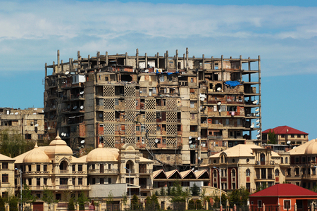 Luxurious brownstone mansions and unfinished frame of high-rise residential building inhabited by poor people in Baku, Azerbaijan. Social inequality illustration.