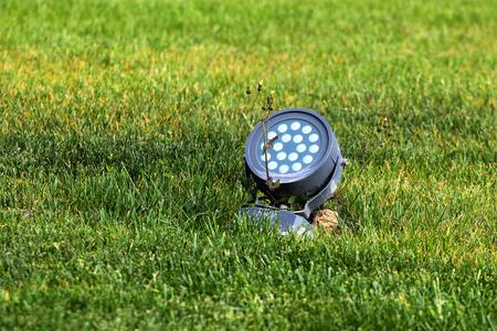 outdoor lighting: Electric spotlight in green grass
