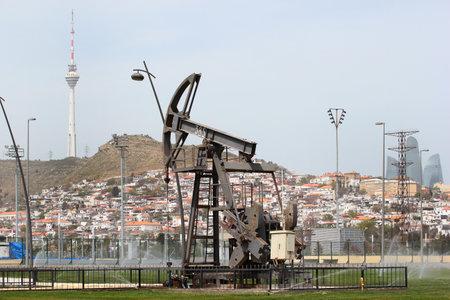 BAKU, AZERBAIJAN - APRIL 28, 2017: Oil pumpjack in Baku seaside park, symbol of wealth and prosperity of Azerbaijan. TV tower and Flame Towers  in background. Editorial