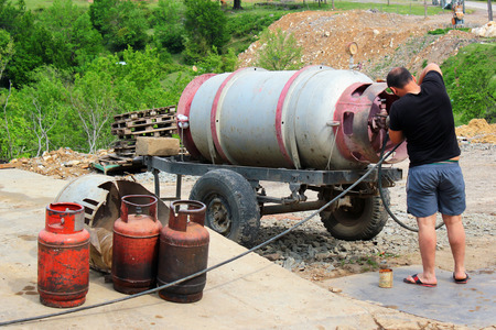 butane: Man refills small propane gas tanks from big barrel on a trailer Stock Photo